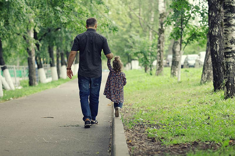 father and kid taking a walk in a park