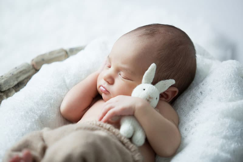 cute newborn sleeping with his toy