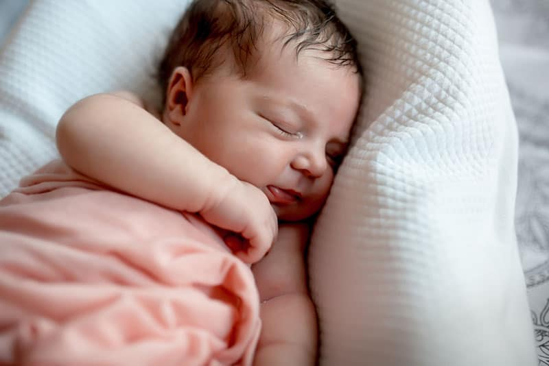 Cute baby sleeping on white pillow
