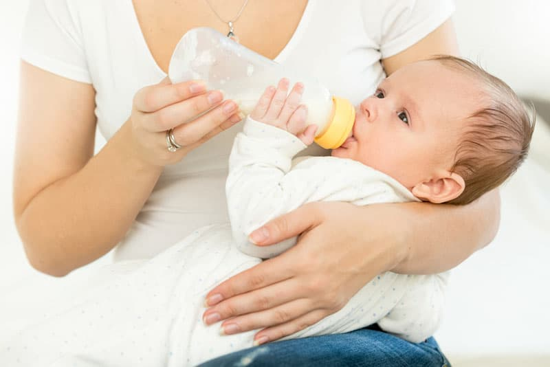 mother feeding her baby with bottle of milk