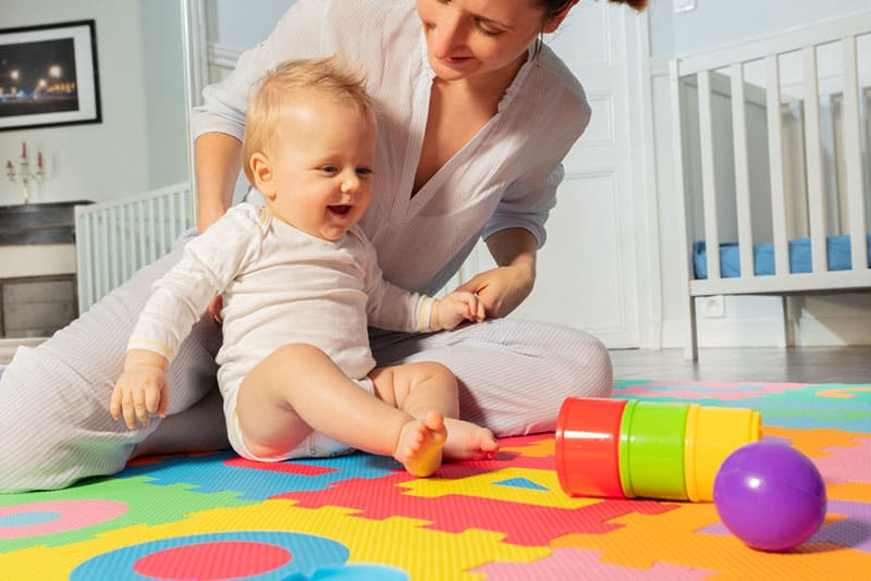 mother playing with baby on the floor
