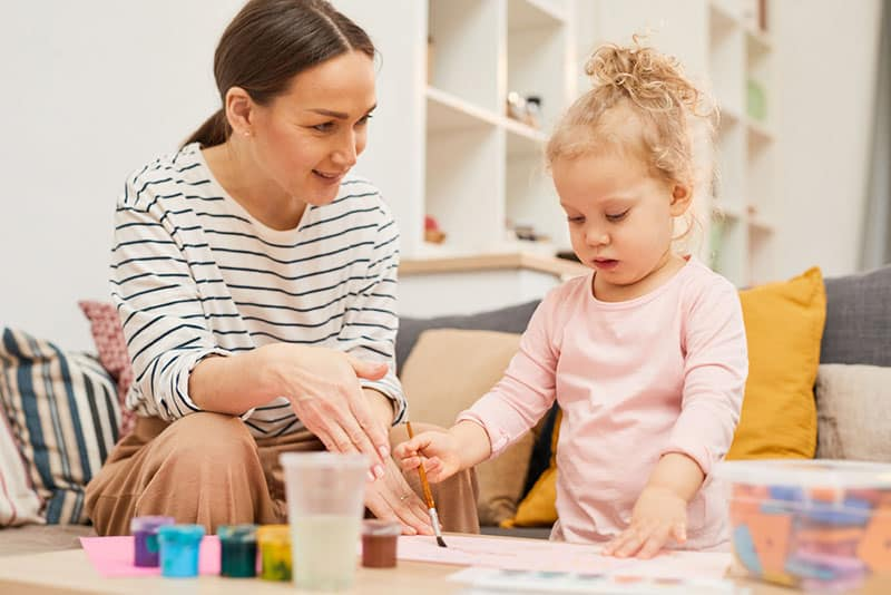 mother teaching daughter how to paint