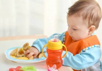 Cute little baby eating sliced fruits at table in room