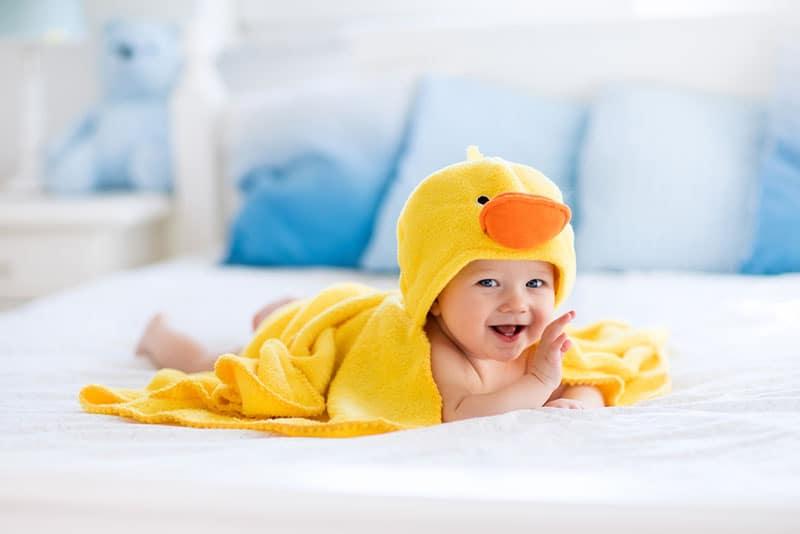 smiling baby wearing duck towel