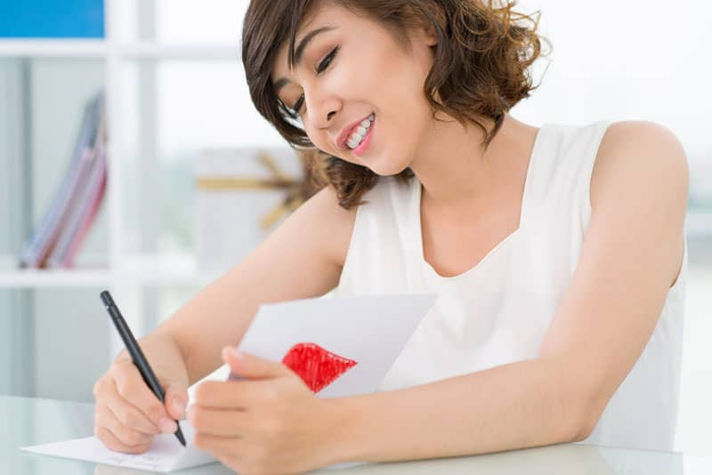 smiling woman writing congratulation card