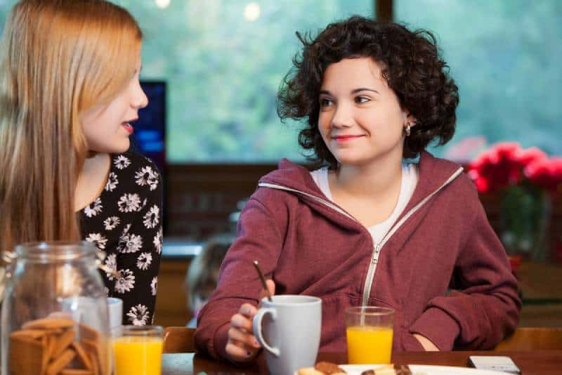 Two happy teen girl friends having breakfast together at home