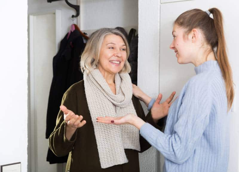 Young and older women having emotional conversation in apartment hallway