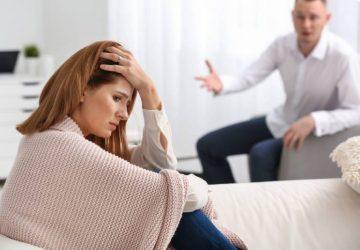 Sad woman sitting on sofa while husband shouting at her