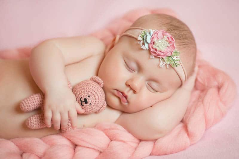 baby girl in pink vintage outfit sleeping