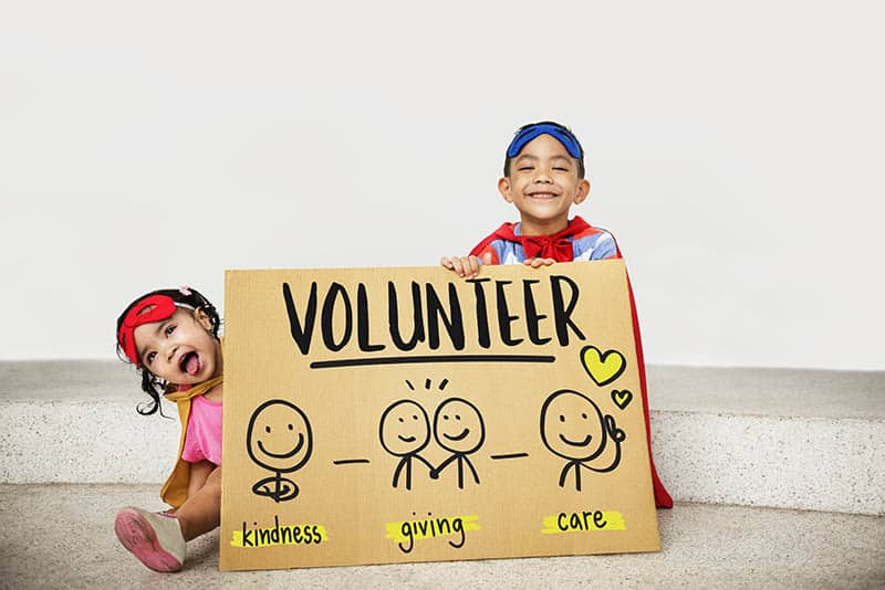 kids holding a sign with volunteer on it