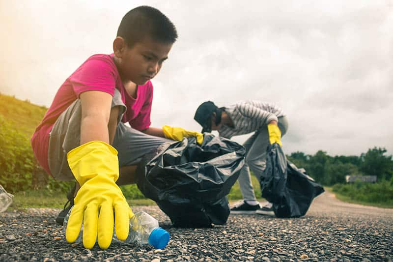 boy helping volunteering by picking up trash cleaning environment