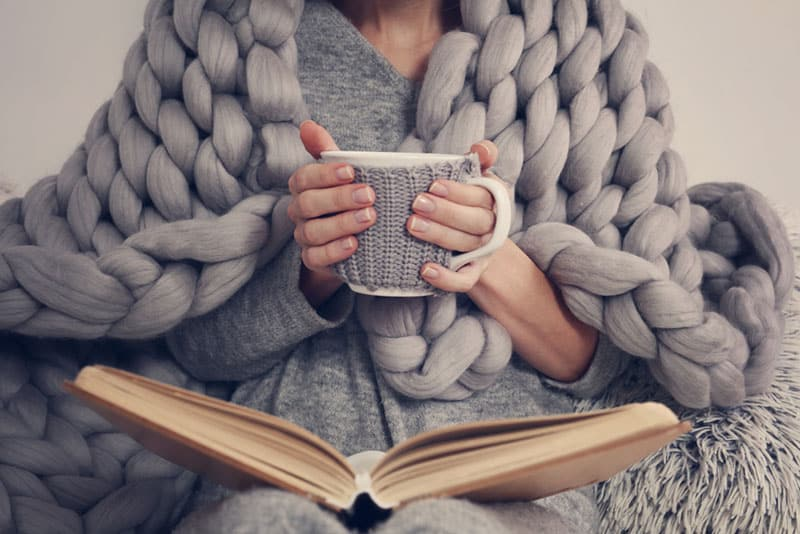 woman covered with blanket drinking coffee and reading a book