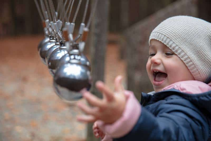 Toddler having fun with a perpetuum mobile at a forrest playground