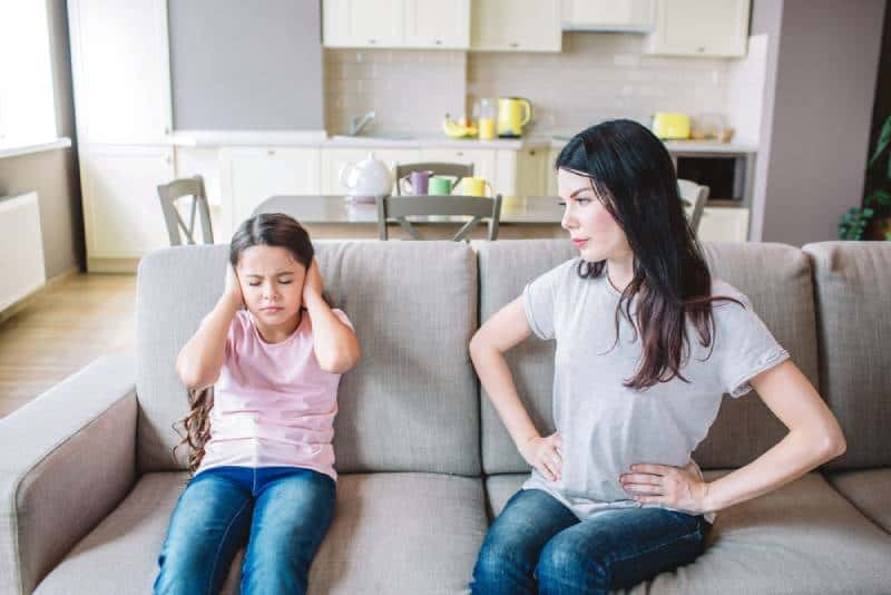 Mother is looking at daughter who ignores her by putting her hands on her ears.