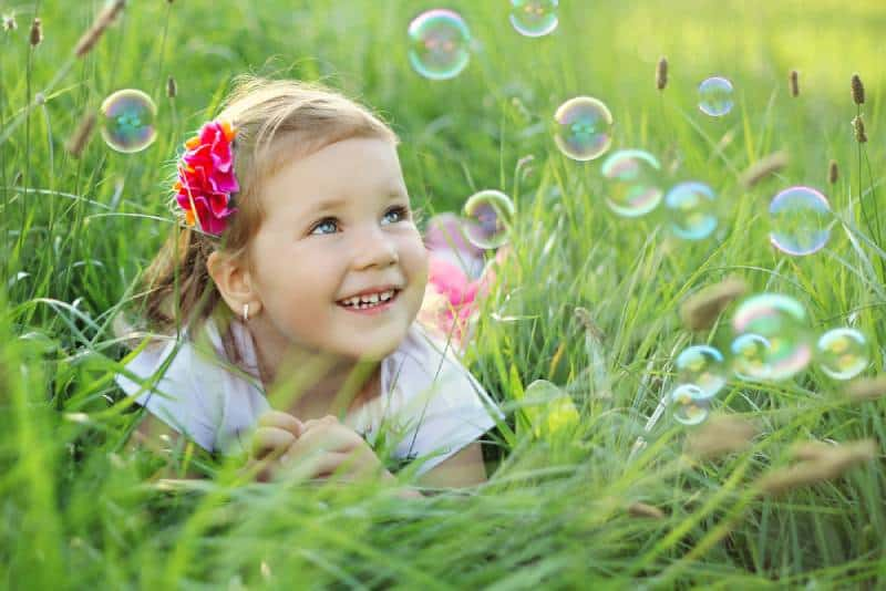 three year old girl laying on a grass in a park playing with bubbles