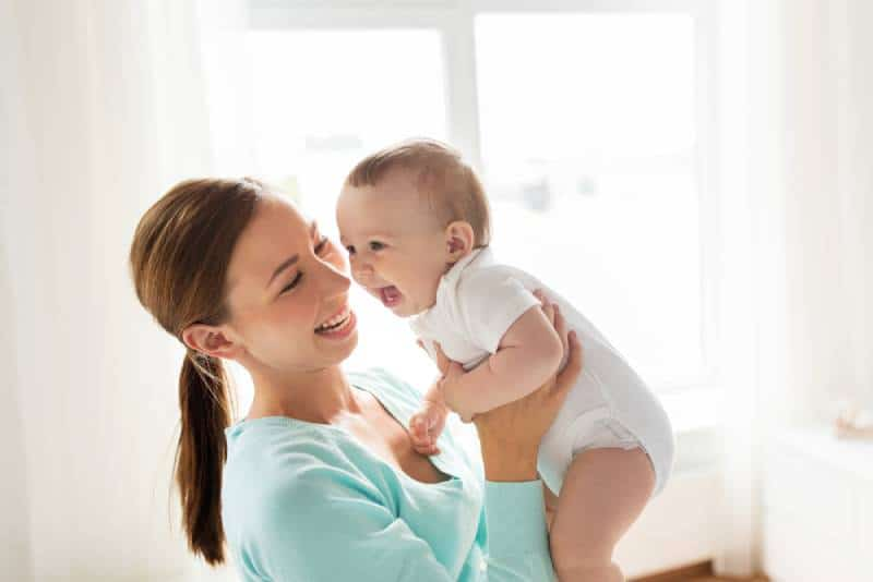 Mom holding baby and smiling indoors
