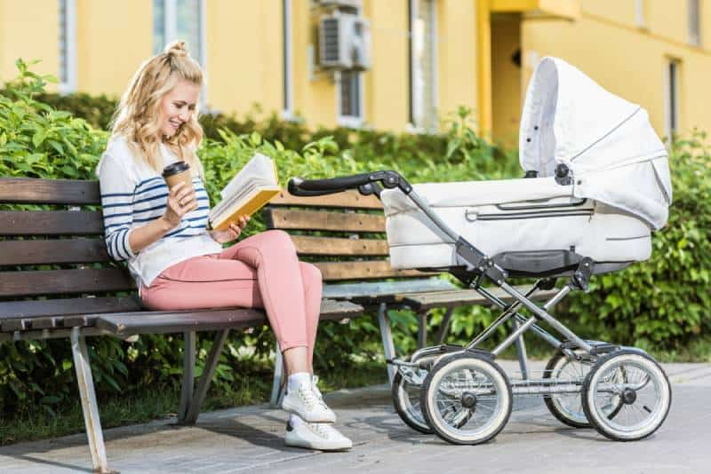 mother reading book and holding coffee to go on bench near baby stroller in park