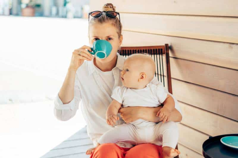 woman sits in a deck chair at the table, drinks coffee and holds the baby in her arms