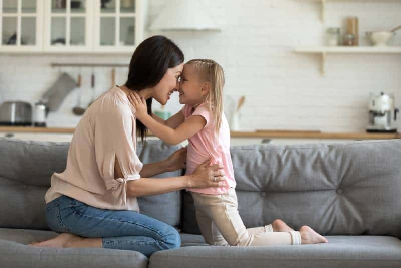 preschooler girl and young mother touch noses foreheads look in eyes enjoy tender sweet moment together