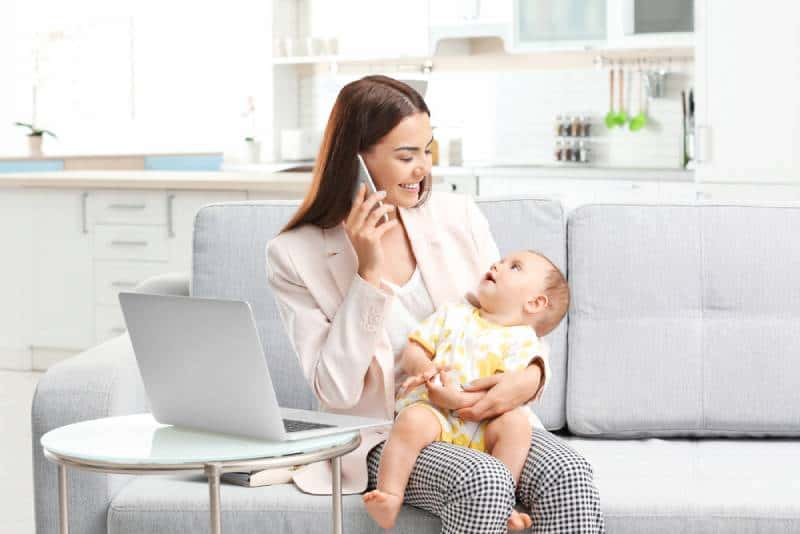 Mom holding baby and talking on phone at home