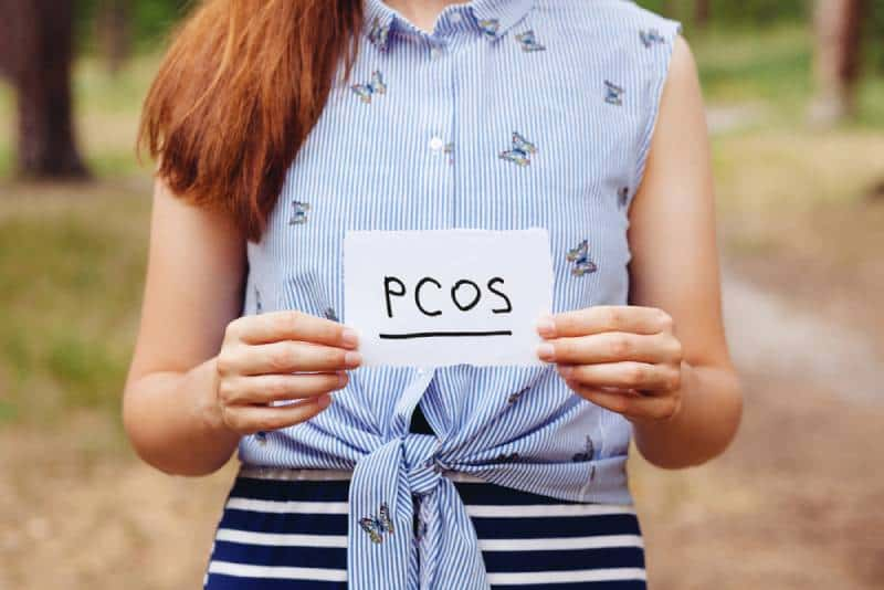 Woman holding pcos sign while standing outside