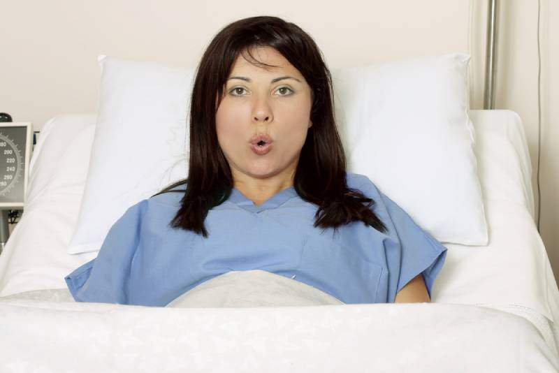 Woman taking long breaths while being in hospital