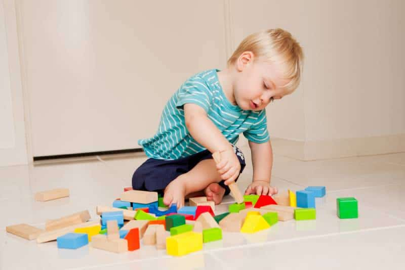 baby boy playing with colorful blocks indoors