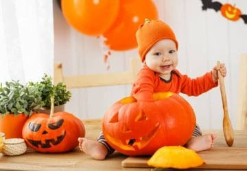 happy baby in costume with a pumpkin for Halloween