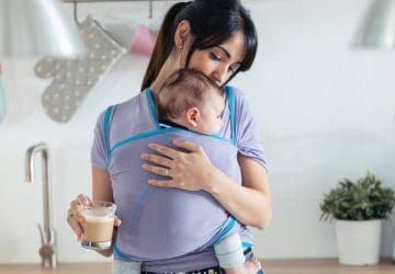 mother with little baby in sling drinking coffee in the kitchen at home