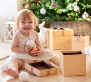 two-year-old girl sits next to an open gift box on the background of the New Year tree and enjoys Christmas toys