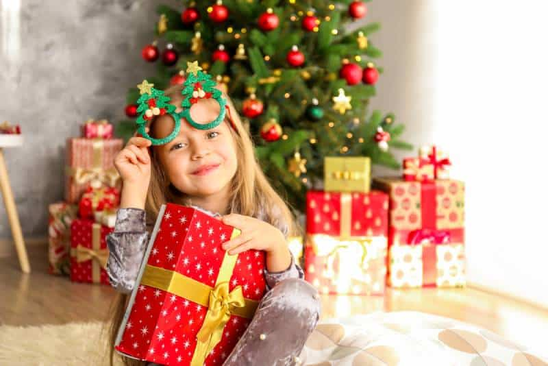Cute girls holding her christmas present next to a decorated christmas tree