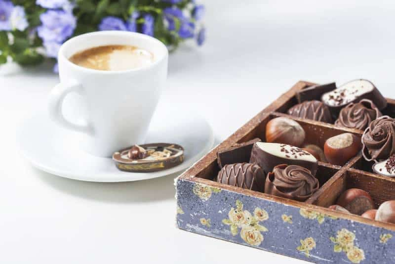 Cup of coffee on a white background with a variety of chocolates in a wooden box