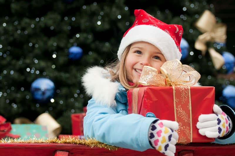 cute girl smiling and holding her christmas present