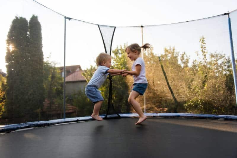 Siblings having fun as they jump on trampoline