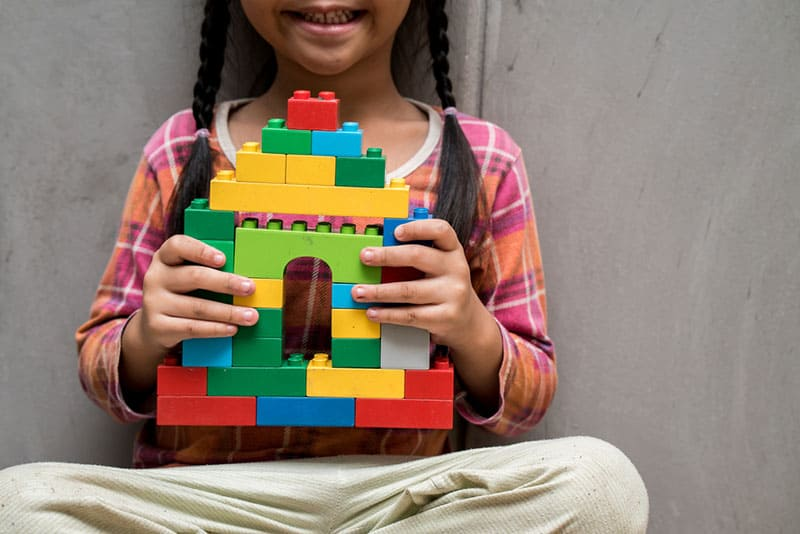 little girl holding lego construction