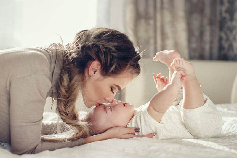 young mother kissing baby on forehead
