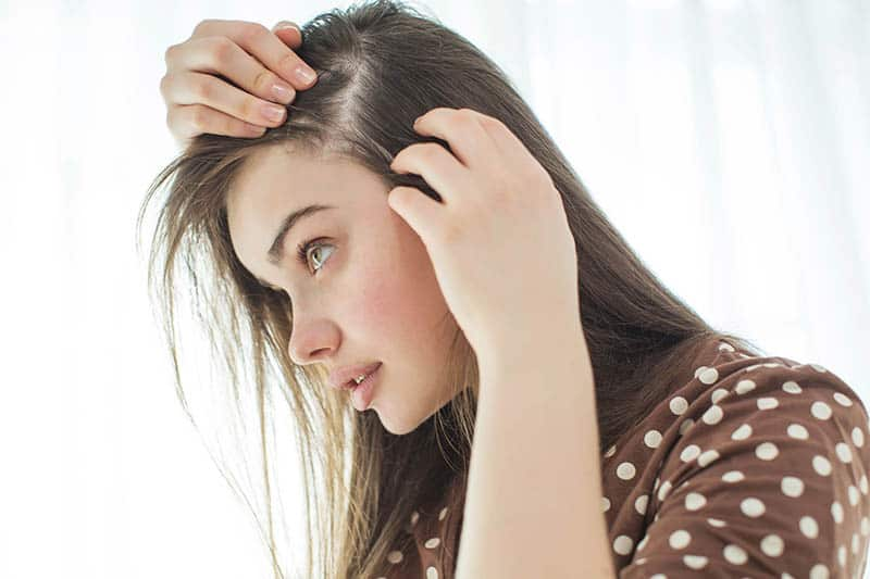 woman checking her hair for hair loss
