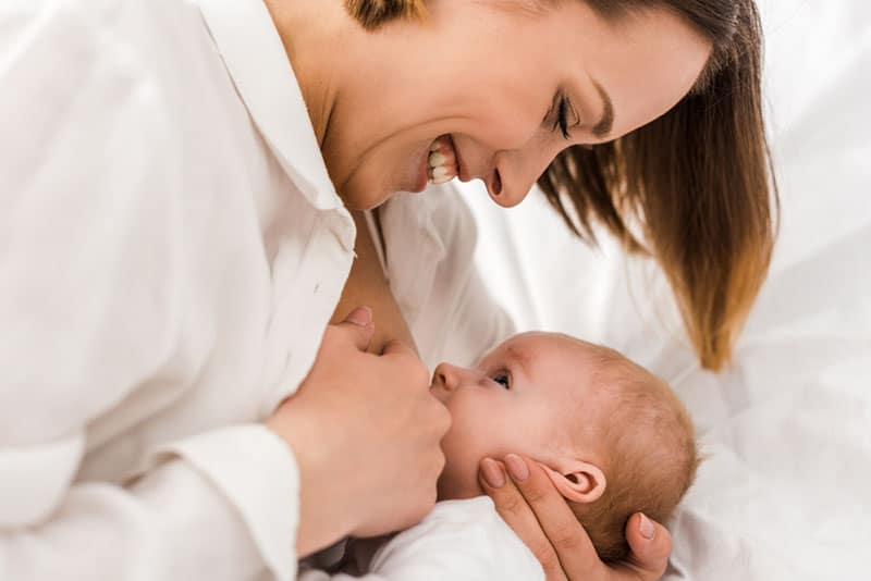 smiling mother breastfeeding her baby