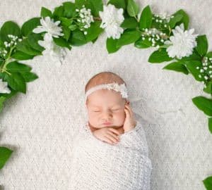 Beautiful newborn girl and flowers