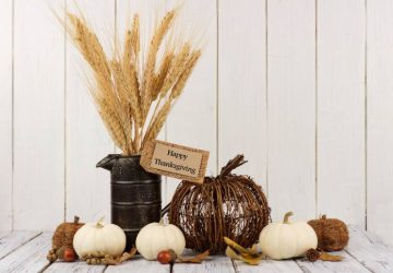 Happy Thanksgiving tag, pumpkins and autumn home decor with a white wood background