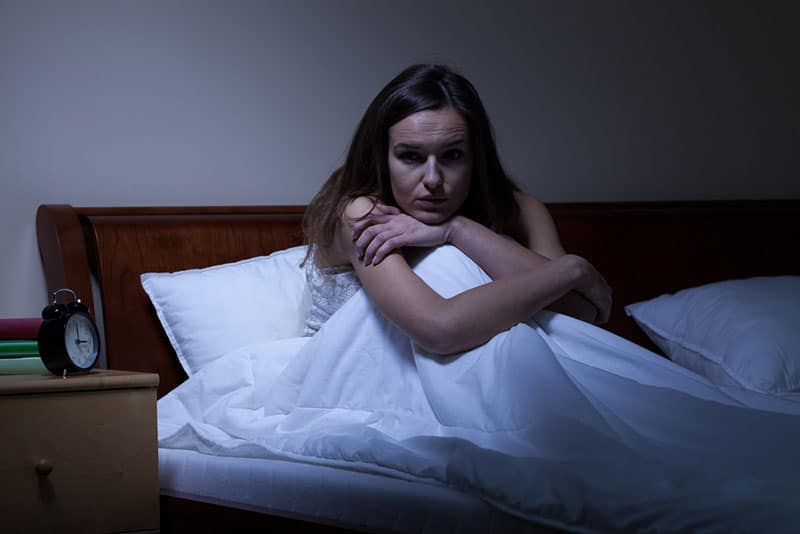 upset woman sitting in bed