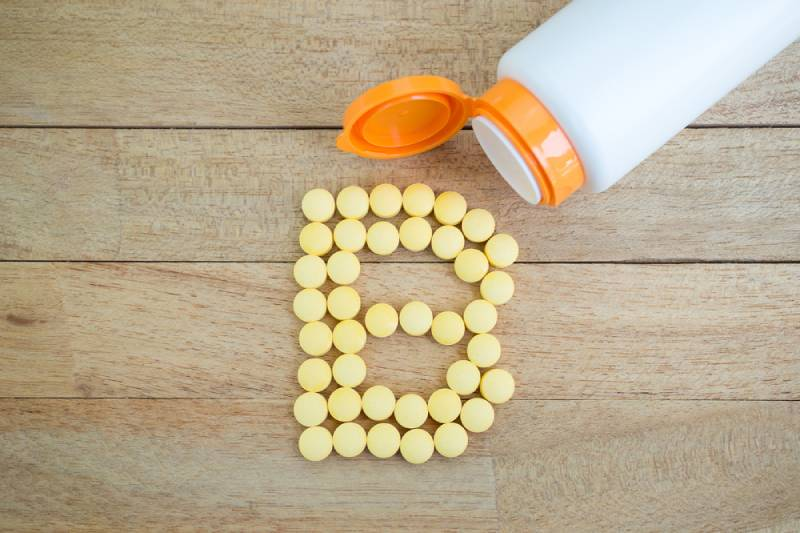 Yellow pills forming shape to B alphabet on wood background