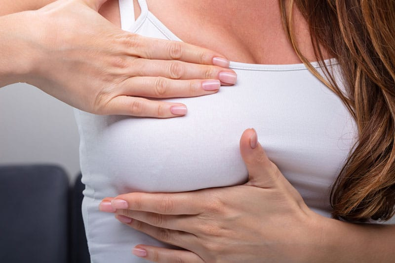 young woman feeling pain in breast
