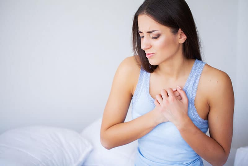 young woman feeling pain in her breasts