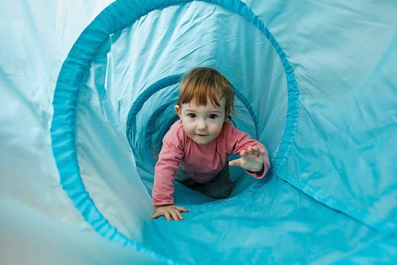 toddler climbing through a tube