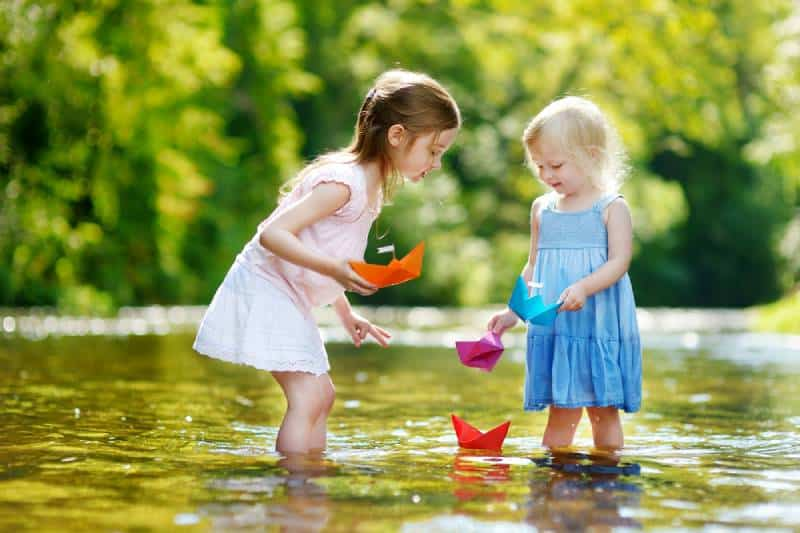 Two adorable little sisters playing with paper boats by a river
