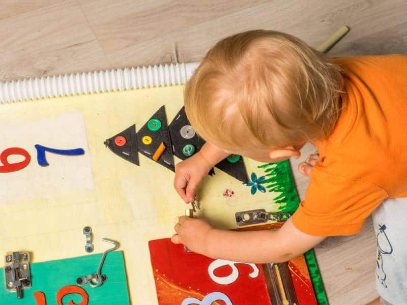 Boy playing with sensory bin on the floor
