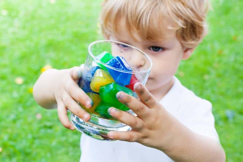 boy in summer garden playing with glass of colorful ice cubes