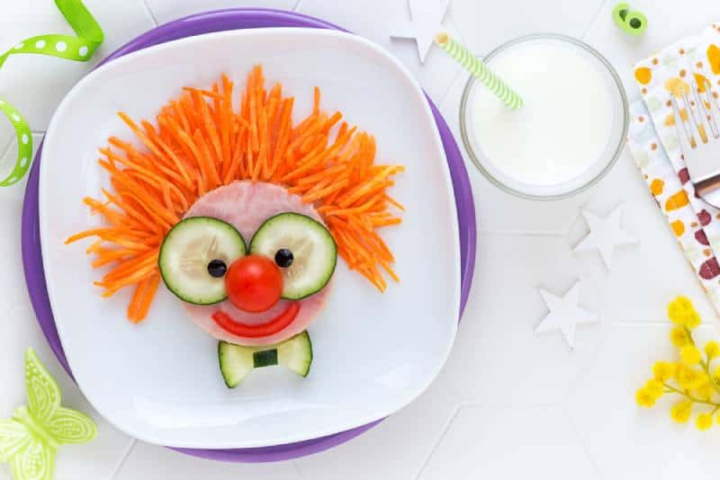cute smiling clown face on ham sandwich decorated with fresh cucumber, carrots and tomatoes
