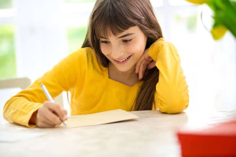 smiling girl in yellow shirt writing a letter sitting at desk